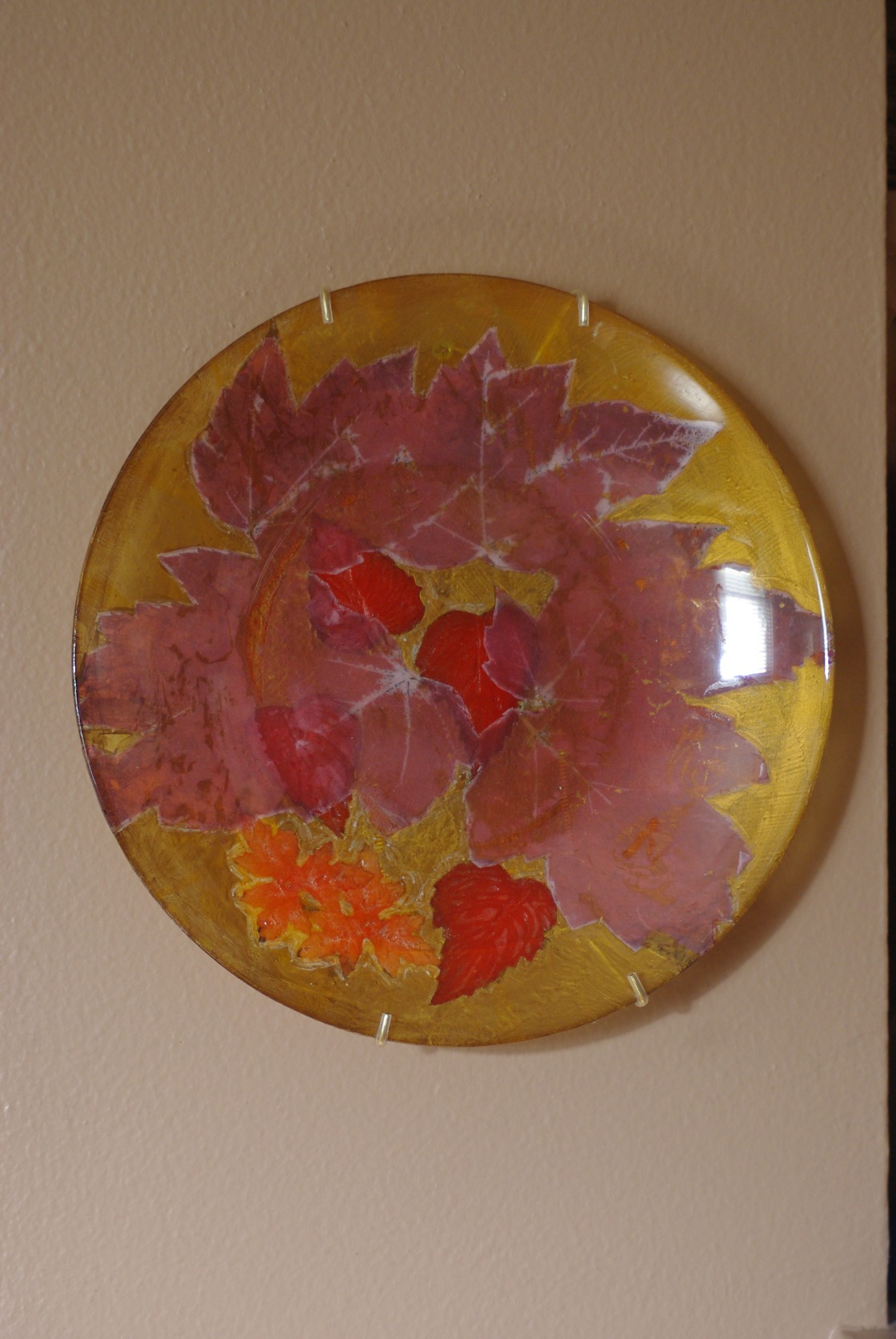 Decorated a cheap glass plate with leaf transfers and silk leaves.  The background is yellow tissue paper.
