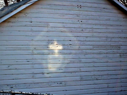 A reflection from ? looking like a cross appeared on the side of an old garage in my neighborhood a few years ago. A light against the grunge.