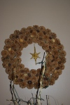 Wreath of pine cones & accented with tiny cones & nuts.