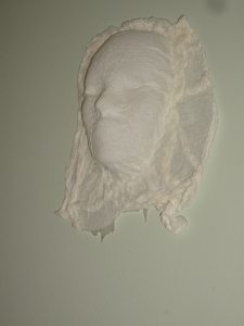 Gauze fabric mask created with white glue over plastic mask mold.