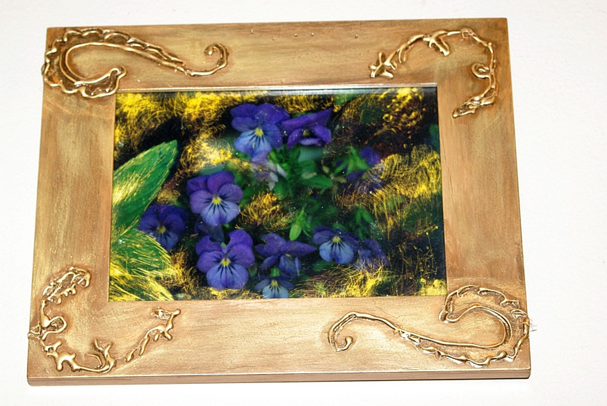Altered photograph in a wood frame with glue gun scrolling and gold paint.