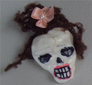 Girl skull pin from air clay & dolls hair.