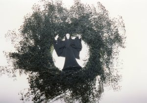 Wreath of baby's breath spray painted black with figure.
