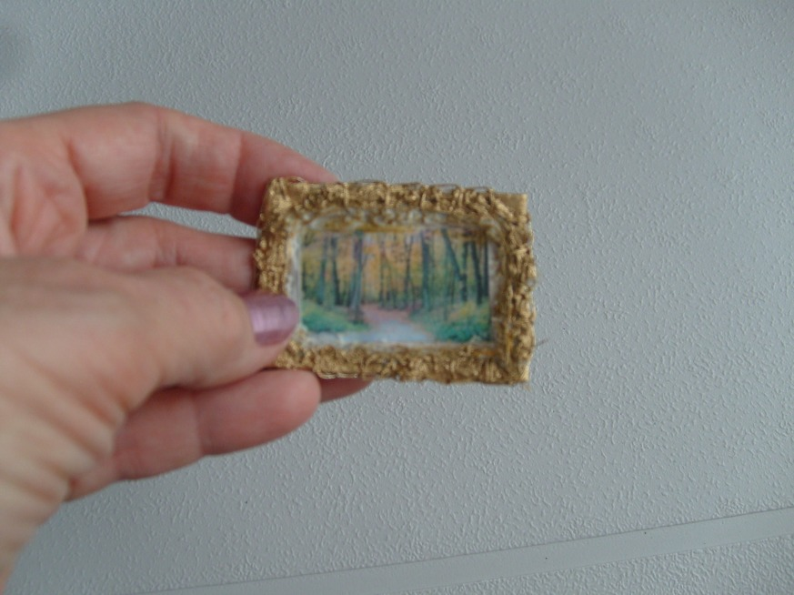 Hand made art pin of woods from fabric transfer and painted lace for the frame.
