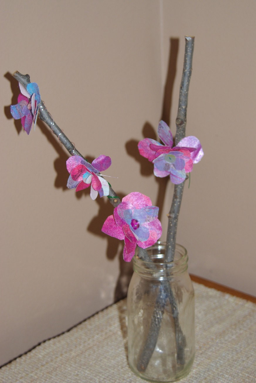 painted fabric flowers attached to branches.